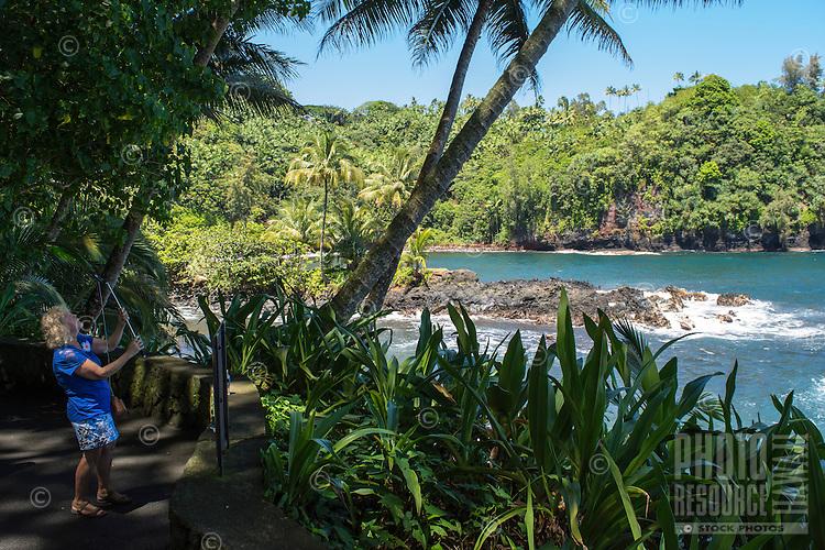 A tourist with a selfie stick takes photos of Onomea Bay and the Hamakua coastline along a trail through Hawaii Tropical Botanical Garden, Big Island of Hawaiʻi.