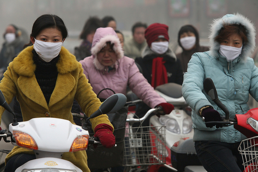 Commuters wear masks to protect themselves from pollution as they ride vicycles to work in Linfen.