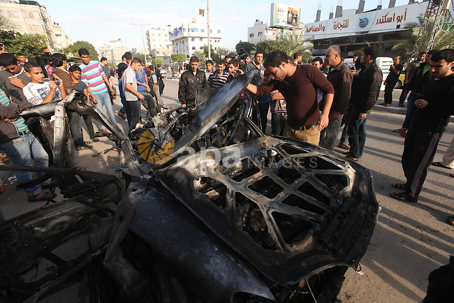 Palestinians gather around a destroyed car which targeted by Israeli airstrike in the northen Gaza city, 19 November, 2012. Israeli aircraft killed A Palestinian and wounded two others in the raid.  Media reports that Israeli forces were on Monday targeting the Palestinian homes and other buildings in its bombardment of the Gaza Strip, as the combined death toll in six days of airstrikes and rocket attacks climbed to nearly 100. Photo by Majdi Fathi