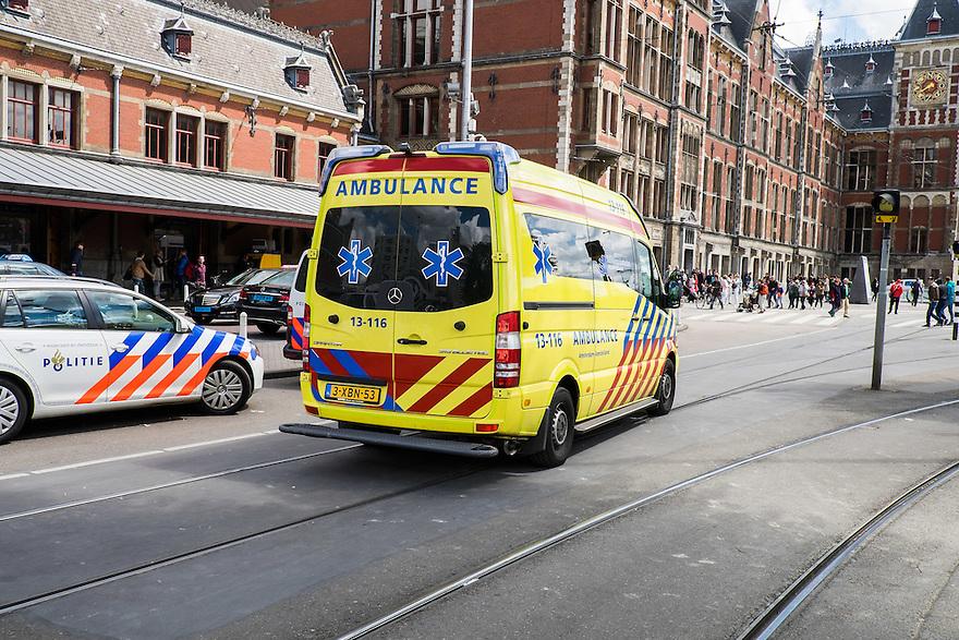 Nederland, Amsterdam, 30 mei 2015<br /> Ambulance komt aanrijden voor het centraal station van Amsterdam omdat er iemand onwel is geworden.<br /> Foto: Michiel Wijnbergh