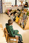 Preschool Headstart New York City 4 year olds time out for boy after misbehavior other children are sitting in circle time listening to female teacher read book vertical