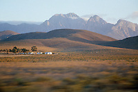 The small whitewashed buildings on the plain are dwarfed by the enormous Outeniqua mountains