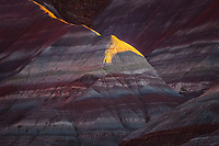 A sliver of sunset light illuminates a small peak the colorful shapes and striations of the Paria desert.