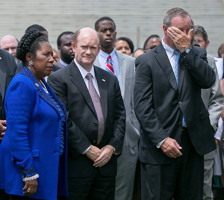 UNITED STATES - JUNE 18 - Rep. Jeff Duncan, R-S.C., right, wipes his face as he stands besides Rep. Sheila Jackson Lee, D-Texas, left, and Sen. Chris Coons, D-Del., during a prayer vigil for victims of the Charleston shooting, outside of the U.S. Capitol on Thursday, June 18, 2015. (Photo By Al Drago/CQ Roll Call)