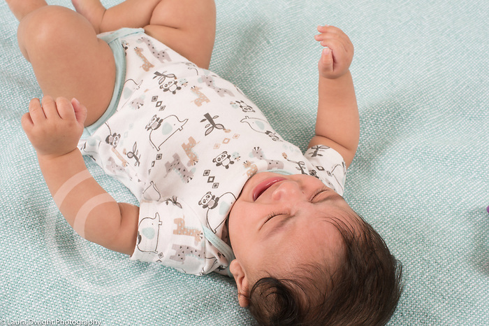 Unhappy, crying 4 month old baby boy on back, closeup