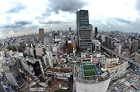 Boys play foot ball on a skyscraper football pitch, Shibuya city from above, Shibuya, Tokyo.<br /> April-2010