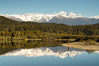 Southern Alps with Mt. Tasman 3497m, Mt. Cook 3724m and hiker reflecting in Three Mile lagoon, Westland Tai Poutini National Park, West Coast, UNESCO World Heritage Area, New Zealand, NZ