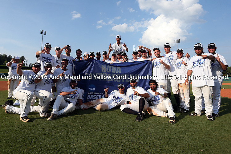 04 June 2016: Nova Southeastern players pose with the championship banner after the game. The Nova Southeastern University Sharks played the Millersville University Marauders in Game 14 of the 2016 NCAA Division II College World Series  at Coleman Field at the USA Baseball National Training Complex in Cary, North Carolina. Nova Southeastern won the game 8-6 and clinched the NCAA Division II Baseball Championship.