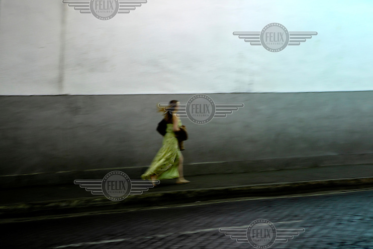 A woman walks along a pavement in central Rome.