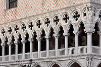 Detail of the Venetian Gothic arcades of the Doge's Palace or Palazzo Ducale, begun 1340, with sculpture of the Angel Gabriel holding a sword on the corner, possibly by Filippo Calendario, on the Piazzetta San Marco, between the Piazza San Marco and the Venetian lagoon, Venice, Italy. The palace has 2 arcades with 14th and 15th century capitals and sculptures, and a loggia above with a decorative brickwork facade. It was the residence of the Doge of Venice, the supreme authority of the former Republic of Venice, until the Napoleonic occupation in 1797, and is now a museum. The city of Venice is an archipelago of 117 small islands separated by canals and linked by bridges, in the Venetian Lagoon. The historical centre of Venice is listed as a UNESCO World Heritage Site. Picture by Manuel Cohen