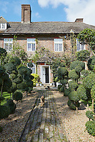 Exterior of a large house from the 1600s, bathed in wisteria. The brick path leading up to the house is flanked by topiary.