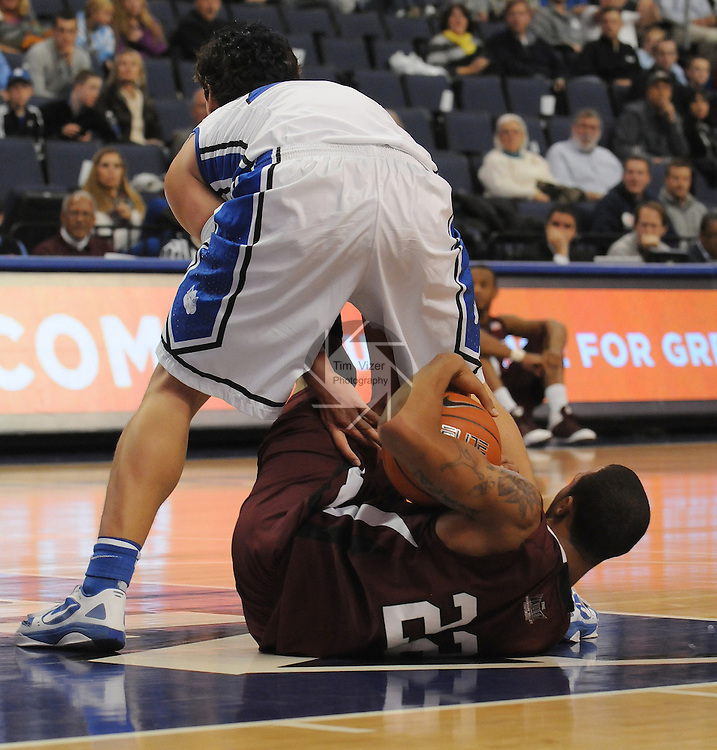 Saint Louis Billikens forward Cody Ellis (24) reaches underneath his body to grab at the ball held by Southern Illinois Salukis guard Jeff Early (22) in first-half action during a non-conference game between the St. Louis University Billikens and the Southern Illinois University-Carbondale Salukis on November 24, 2012 at the Chaifetz Arena in St. Louis Missouri.  The Billikens won, 61-51.