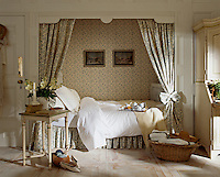 A traditional bedroom with a bed set in a recess. Floral pattern curtains screen the bed and match the wallpaper behind.