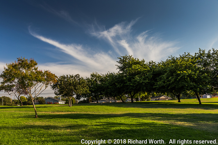 Wispy clouds in a blue sky on a late summer afternoon at a neighborhood park.
