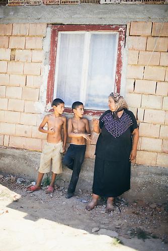 Remus (l) und Livio* (m), die Enkel von Parashiva Lakatar (r). Danuţ streitet sich gerade mt seiner Grossmutter. Europa, Rumaenien, Rusciori den 25. Juli 2015
