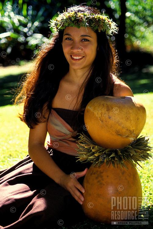 Young smiling Hawaiian hula dancer with ipu heke instrument in a park in Honolulu on Oahu