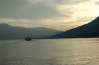 Ferry crosses Kootenay Lake, BC heading west at sunset.