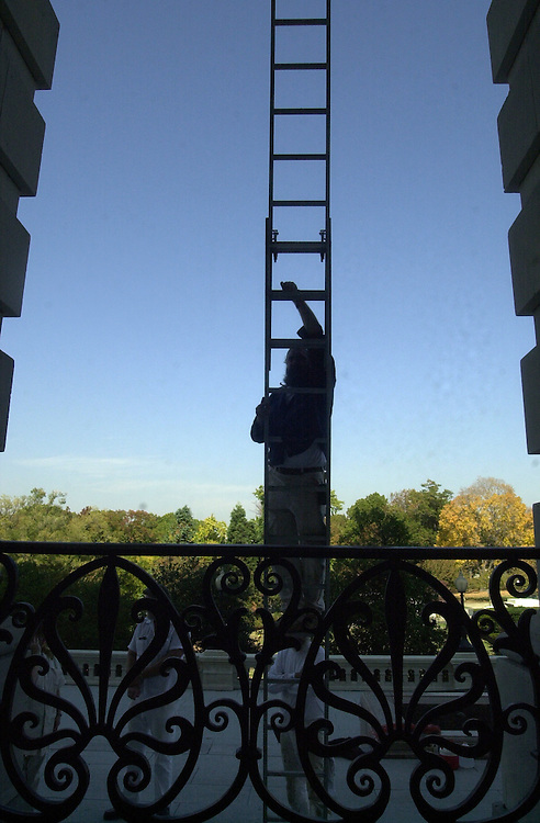 1window102401 -- Rick Marvel scales a ladder to replace a window on the northl side of the U.S. Capitol before a mylar window coating is installed.