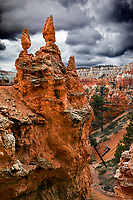 Hundreds of rock formations called Hoodoos can be found at Bryce Canyon National Park.  Nearly 180 days of freezing and thawing of water in the rock fractures primarily cause these statuesque features.  The challenge is to find your favorite formation.  While descending the Queens Garden Trail, I came upon these twin pillars precariously balanced on the rock wall.  Nice reflected light illuminates the entire formation while storm clouds form in the background.