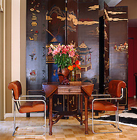 A pair of modern chrome and leather chairs and a hexagonal wooden table have been placed in front of a Chinoiserie screen in the living area