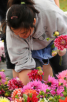 A woman works at a flower stand at the Puyallup Farmer's Market in Puyallup, Washington.