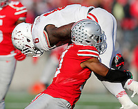 Ohio State Buckeyes defensive back Vonn Bell (11) slams down Indiana Hoosiers running back Tevin Coleman (6) in the fourth quarter of the college football game between the Ohio State Buckeyes and the Indiana Hoosiers at Ohio Stadium in Columbus, Saturday afternoon, November 22, 2014. The Ohio State Buckeyes defeated the Indiana Hoosiers 42 - 27. (The Columbus Dispatch / Eamon Queeney)