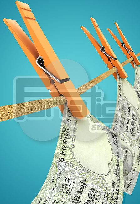 Conceptual image of currency hanging on rope with clothespin representing money laundering