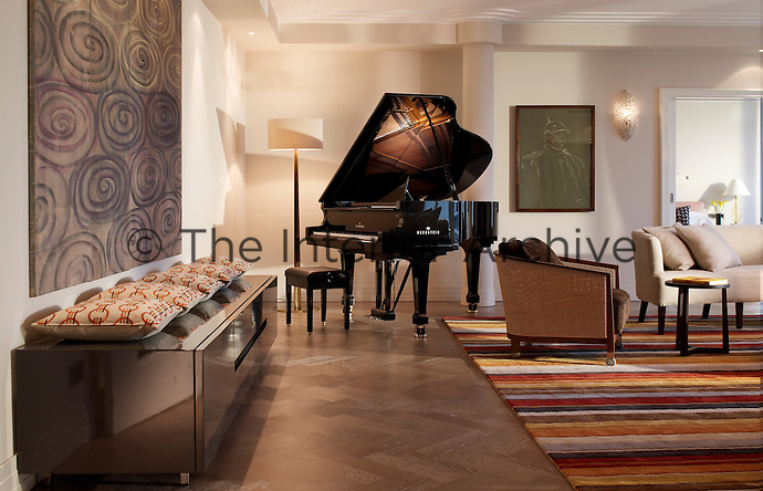 A large suite of the Charles Hotel, Munich is furnished with a grand piano in one corner juxtaposed with contemporary furniture and works of art