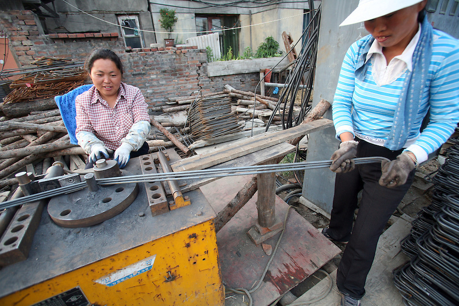 Women workers shape bars of steel in Mudanjiang in China's northern Heilongjiang province, July 4, 2006. The government is seeking to avoid a sudden economic slowdown in the world's biggest market for steel and second-largest oil user by shifting its focus to raising incomes and consumer spending.