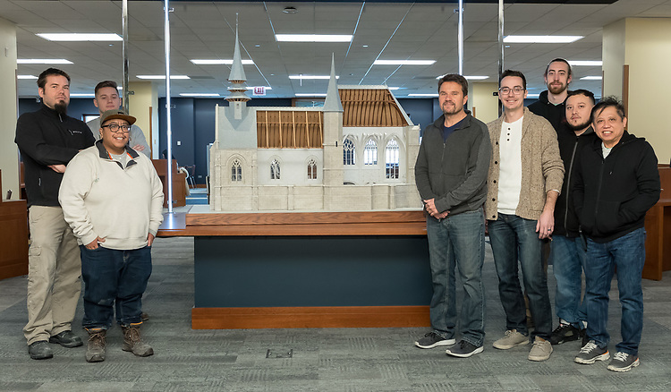 Employees from Presentation Studios International, an architectural and engineering model maker based in Chicago, with a scale model of the Church at Folleville, France, on display on the second floor of the Richardson Library on the Lincoln Park Campus. The church is where on Jan. 25, 1617, St. Vincent de Paul preached a sermon which led to the foundation of the Congregation of the Mission and all of his works. The model captures what the church looked like on that day. The church is still in existence but has undergone many changes over its 500 year history. (DePaul University/Jeff Carrion)