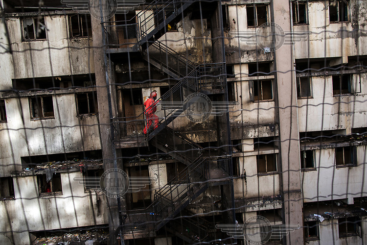 A member of the Red Ants climbs a stairway at Fatti's Mansions on Jeppe Street during an operation to clear the block of its illegal occupants. The Red Ants are a controversial private security company often hired to clear squatters from land and so-called 'hijacked' properties.