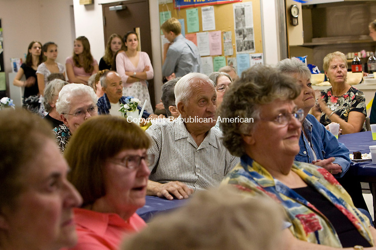 WINSTED, CT - 21 MAY 2010 -052110JT19-<br /> Winsted Senior Center members listen to music from the Gilbert School's Barbershop singers during a senior spring soiree, sponsored by the National Honor Society at The Gilbert School, whose members are pictured in the background, on Friday. The event also featured the Gilbert women's choir, the jazz band, and dance lessons.<br /> Josalee Thrift Republican-American