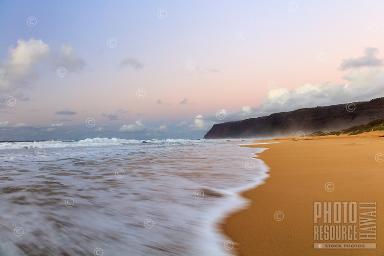The sky turns to the cooling colors of pink and blue as the surf washes onto Polihale Beach at Polihale State Park, Kauai.