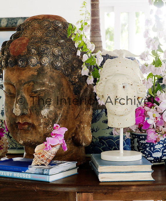 A head of Buddha is juxtaposed with a classical head in this compositon on the library table in the living room