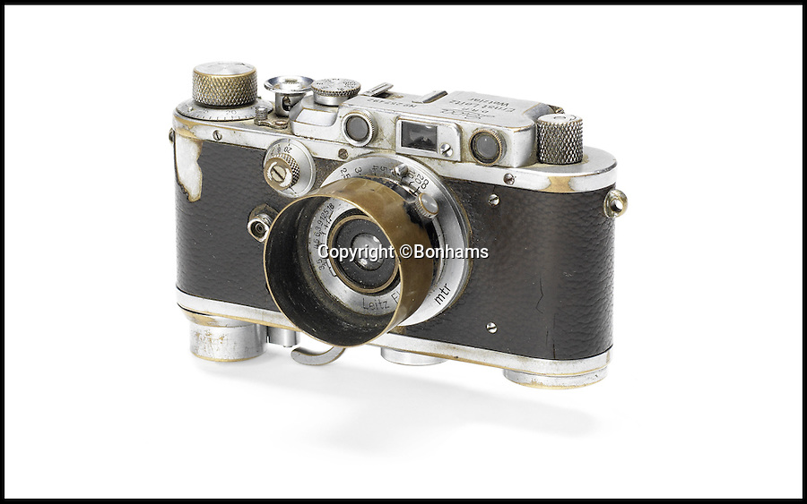 BNPS.co.uk (01202 558833)<br /> Pic: Bonhams/BNPS<br /> <br /> ***Use Full Byline***<br /> <br /> Yevgeny Khaldiei with his Leica that is up for auction, which is estimated between £230,000 - 340,000. The camera is up for auction on November 30th at Bonhams Leica Centenary Sale in Hong Kong.<br /> <br /> <br /> A camera which took one of the most iconic photographs of the Second World War has emerged for sale for 340,000 pounds.<br /> <br /> The Leica camera belonged to Soviet photographer Yevgeni Khaldei who was with the Red Army when they captured Berlin in May 1945, bringing about an end to WWII.<br /> <br /> Khaldei scaled the Reichstag on May 2 to capture on camera a soldier raising the Red Banner, the Soviet flag, to claim the symbolic building as under their control.<br /> <br /> In fact it was a restaging of a moment which had happened two days previously but resilient Nazi fighters had taken the original flag down overnight.<br /> <br /> The final image was heavily edited to add more smoke to the scene and also cover up the watches on the wrists of the soldiers which had been looted.<br /> <br /> It went on to become one of the most famous images of the war and was reproduced in publications around the world.<br /> <br /> It is often compared to the photograph of US troops raising the Stars and Stripes on the Japanese island of Iwo Jima.<br /> <br /> The camera is now tipped to fetch 340,000 pounds when it goes under the hammer at Bonhams.