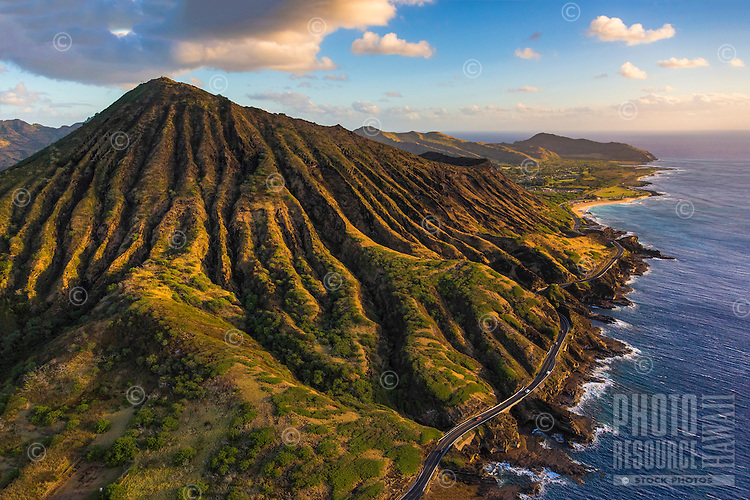Sunrise lights Koko Crater, a popular hiking spot in East O'ahu, with Kalaniana'ole Highway along the coastline and Makapu'u point in the distance.