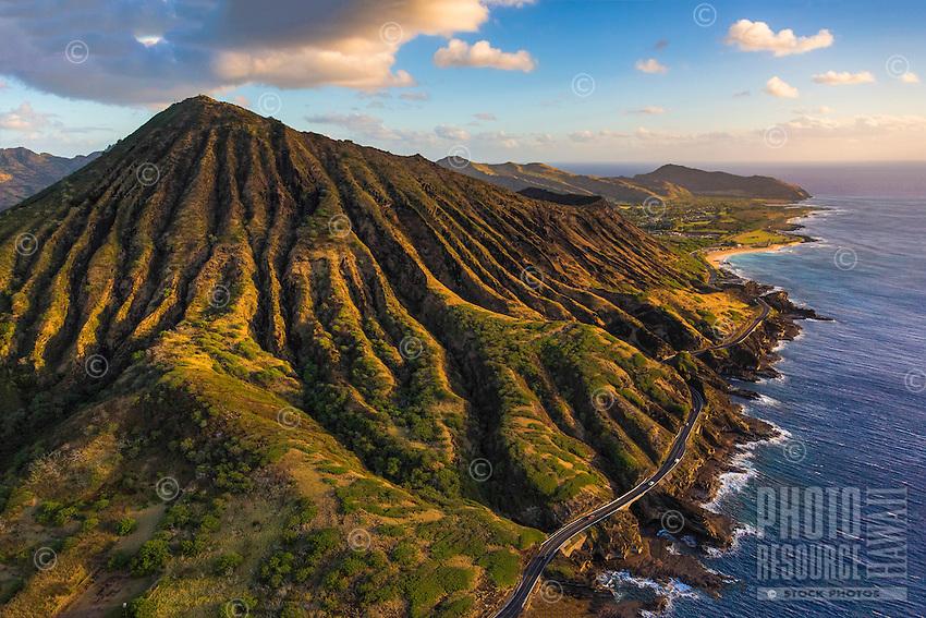 Sunrise lights Koko Crater, a popular hiking spot in East O'ahu, with Kalaniana'ole Highway along the coastline and Makapu'u point in the distance.