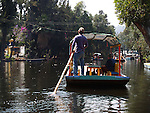 [UNESCO WORLD HERITAGE SITE]<br /> <br /> BOATSMAN STEERS PASSENGERS ALONG LAKE XOCHIMILCO and the FLOATING GARDENS<br /> <br /> Xochimilco is one of the sixteen boroughs within Mexican Federal District. Today,the borough consists of eighteen neighborhoods along with fourteen villages that surround it. While the neighbhoods are somewhat in the geographic center of the Federal District, it is considered to be &ldquo;south&rdquo; and has an identity separate from the historic center of Mexico City. Xochimilco is best known for its canals, which are left from what was an extensive lake and canal system that connected most of the settlements of the Valley of Mexico. These canals, along with artificial islands called chinampas, attract tourists and other city residents to ride on colorful gondolas called<br /> &ldquo;trajineras&rdquo; Its Hispanic past, has made Xochimilco a World Heritage Site.