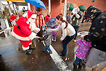 Santa Claus arrives on the Ione Fire Department's ladder truck on Main Street and greats local children in California's Mother Lode.