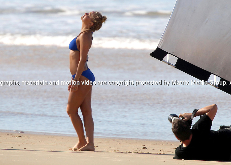 7 AUGUST 2013 SYDNEY AUSTRALIA<br /> <br /> EXCLUSIVE PICTURES<br /> <br /> Lara Bingle pictured on location for a Cotton On campaign photoshoot at a beach north of Noosa. Lara was seen to be enjoying a few tokes on a cheeky cigarette.<br /> <br /> *No internet without clearance*.MUST CALL PRIOR TO USE +61 2 9211-1088. Matrix Media Group.Note: All editorial images subject to the following: For editorial use only. Additional clearance required for commercial, wireless, internet or promotional use.Images may not be altered or modified. Matrix Media Group makes no representations or warranties regarding names, trademarks or logos appearing in the images.