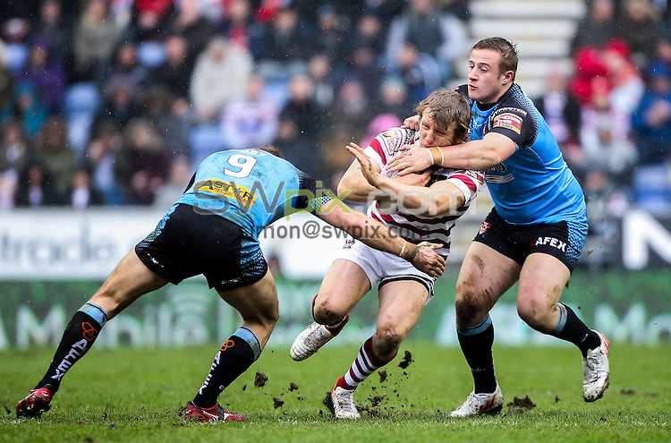 Picture by Alex Whitehead/SWpix.com - 03/04/2015 - Rugby League - First Utility Super League - Wigan Warriors v St Helens - DW Stadium, Wigan, England - Wigan's Logan Tomkins is tackled by St Helens' James Roby and Greg Richards.