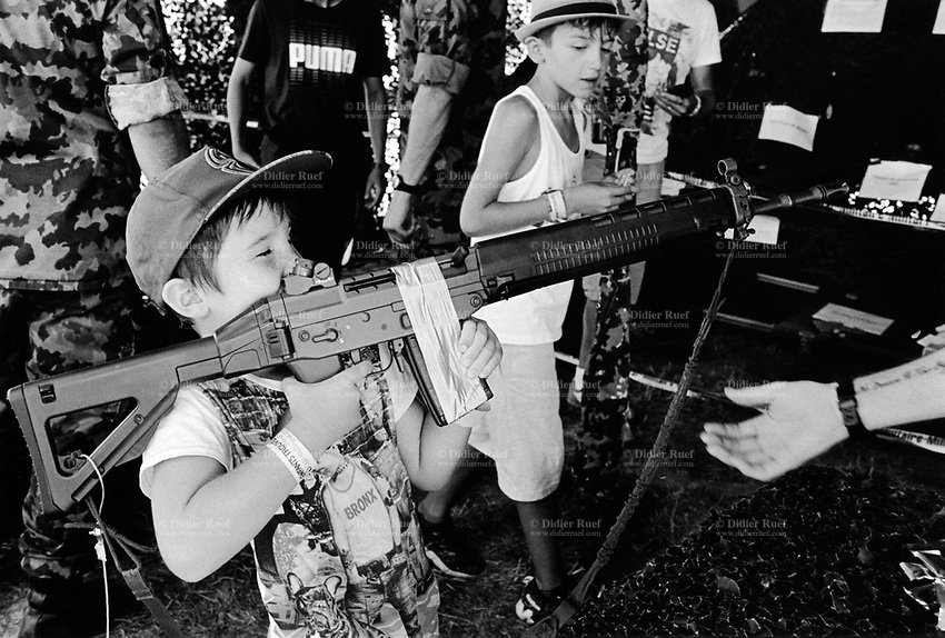 """Switzerland. Canton Fribourg. Estavayer. A young boy is playing with an automatic or semi-automatic assault rifle SG 550 at a swiss army stall during the Federal Wrestling and Alpine Games Festival. The SG 550 is an assault rifle manufactured by Swiss Arms AG (formerly Schweizerische Industrie Gesellschaft) of Neuhausen, Switzerland. """"SG"""" is an abbreviation for Sturmgewehr, or """"assault rifle"""". The rifle is based on the earlier 5.56mm SG 540 and is also known as the Fass 90 or Stgw 90. An assault rifle is a selective-fire rifle that uses an intermediate cartridge and a detachable magazine. 27.08.2016 © 2016 Didier Ruef"""