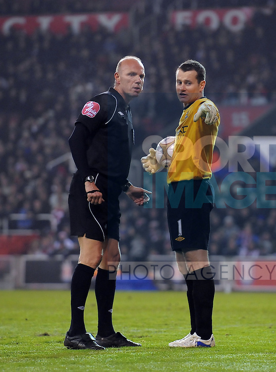 Shay Given of Manchester City complains to referee Steve Bennett  and points to an object thrown from the crowd