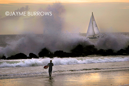 Photo by Jayme Burrows ©2005..Huge waves frame a sailboat at Venice Beach, California on Thursday January 27, 2005. (01/27/05) ..