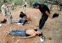 BORSTAR agents Robert Kiernan, left, and Lance Dehler tends to patients as Alberto Nolasco Vazquez tyries to cool his friend off while being rescued form the desert June 4, 2006.Photo by Pat Shannahan