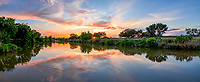 Texas Hill Country Sunset Panorama -<br /> Texas hill country sunset panorama along the Pedernales river landscape.  The sun was just setting and back lit these clouds which were reflected nicely into the water along the river. The pedernales river is a tributary of the Colorado river and flows approximately 106 miles into Central Texas region.  The river flow through the hill country from springs near Kimble County east through Fredericksburg through Blanco County through Stonewall, LBJ Ranch,  Johnson City, and continues it flow  into Lake Travis on the west side of Travis County in Central Texas. We got some nice colors in the sky as the sun set through the trees along the banks in this rural landscape scene.