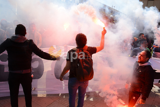 "Al-Zamalek soccer club fans known as 'Ultras White Knights"" light flares and shout slogans during a protest against interior ministry after the riot that killed more than 20 soccer fans last month, at Cairo University on March 2, 2015. Photo by Amr Sayed"