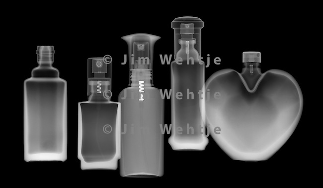 X-ray image of five perfume bottles (white on black) by Jim Wehtje, specialist in x-ray art and design images.