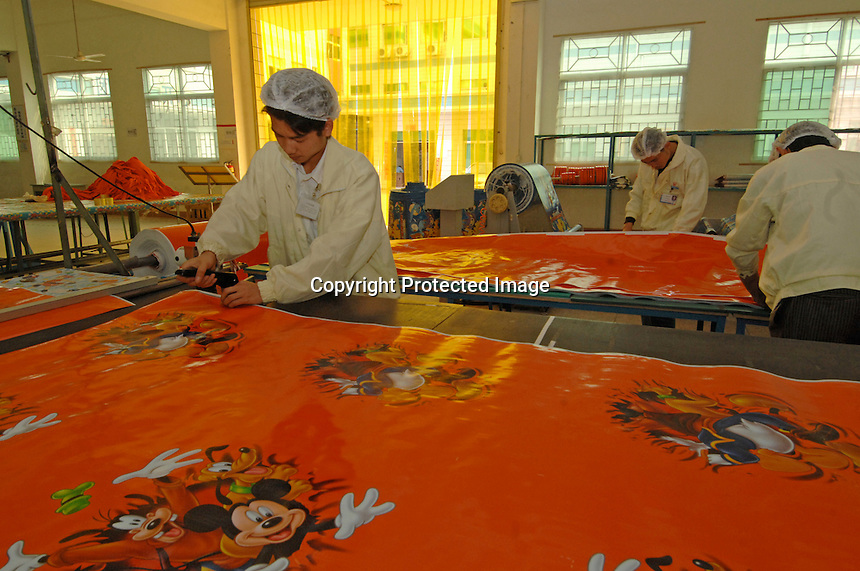 Workers make Pokeman and Disney woven plastic carrier bags at the Richall factory. The woven plastic bags can be used many times and are seen as environmentally friendly. The comapny makes plastic bags for several clients including Disney and Sainsbury's.<br /> <br /> Photo by Richard Jones / Sinopix