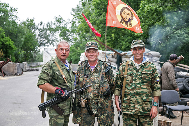 UKRAINE, 27.06.2014, Staniza. Der Separatistenkaempfer Sergej (links) an der Strassensperre des Dorfes Stanitza, ca. 20 km vor Lugansk. Der Kontrollpunkt schuezt die wichtige Bruecke ueber den Fluss Sewerski Donetz. | Separatist fighter Sergey (to the left) at the village Stanytsa blockpost, some 20km from Luhansk city. The blockpost guards an important bridge across the Seversky Donets river. <br /> &copy; Arturas Morozovas/EST&amp;OST